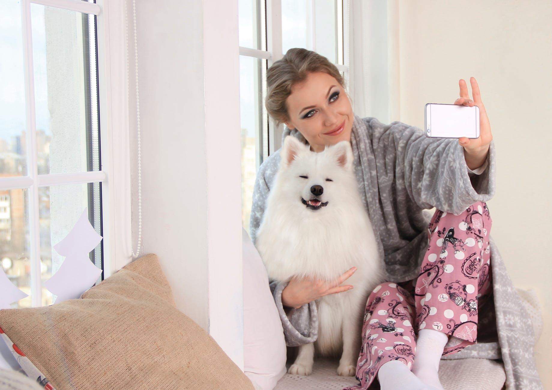 fotke koje sheramo na društvenim mrežama  woman taking a photo of herself with white dog